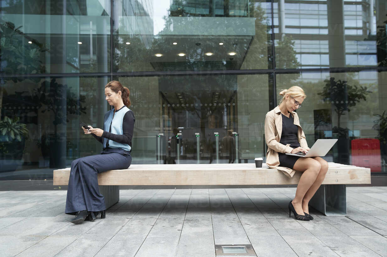 Businesswoman and colleague working while sitting with social distance on bench against office building exterior - PMF01385 - Pete Muller/Westend61