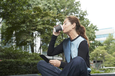 Businesswoman drinking coffee while using mobile phone at office park - PMF01388
