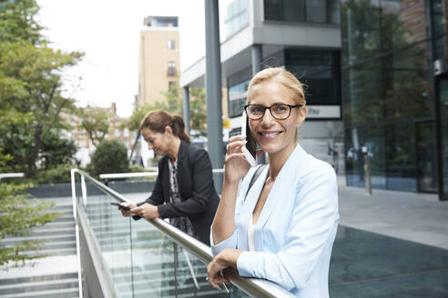 Smiling woman talking on mobile phone while colleague standing in background at city - PMF01394