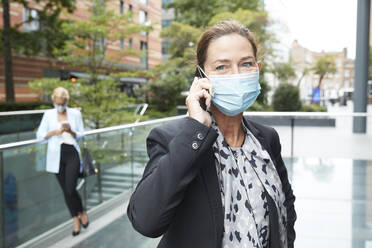 Businesswoman wearing face mask talking on phone with colleague standing in background at city - PMF01400