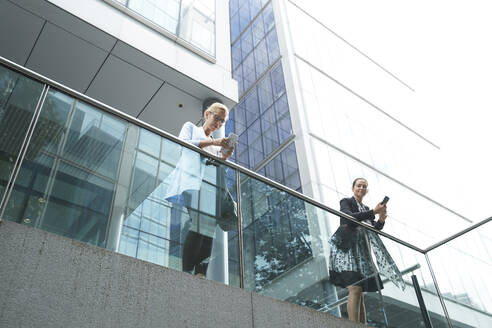 Women using mobile phone while leaning on railing against building - PMF01403