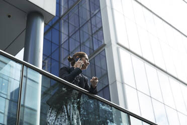 Businesswoman talking on mobile phone while leaning on railing against building - PMF01406