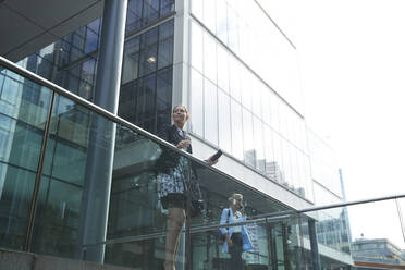 Businesswoman standing by railing with colleague talking on mobile phone in background at city - PMF01409