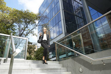 Woman looking away while walking on staircase against building - PMF01412