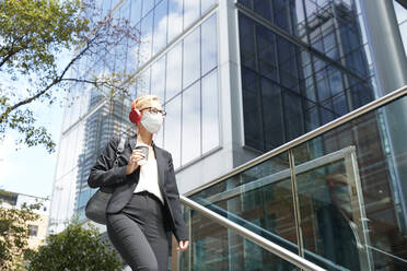 Woman wearing face mask listening music while walking against building - PMF01415