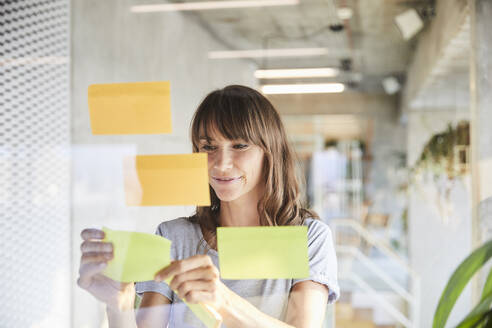Smiling mature woman sticking adhesive notes on glass material - FMKF06512