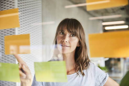 Mature woman pointing sticky notes stick on glass material - FMKF06515