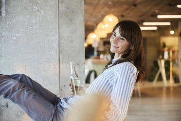 Smiling woman looking away while holding beer bottle sitting on chair at home - FMKF06551