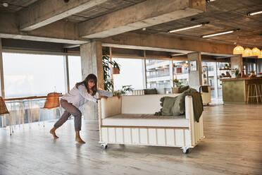 Mature woman pushing sofa at home - FMKF06557
