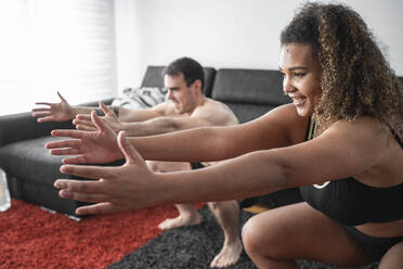 Couple crouching while exercising together at home - SNF00622