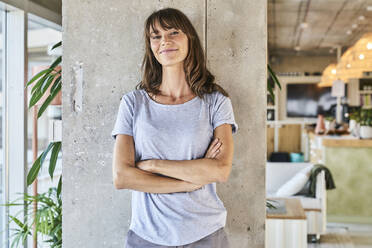 Confident woman standing with arms crossed against wall at home - FMKF06619