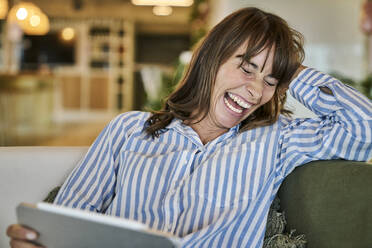 Woman laughing while using digital tablet at home - FMKF06628