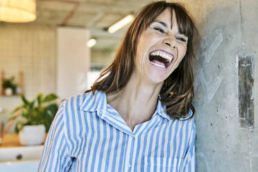 Woman laughing while leaning on wall at home - FMKF06634