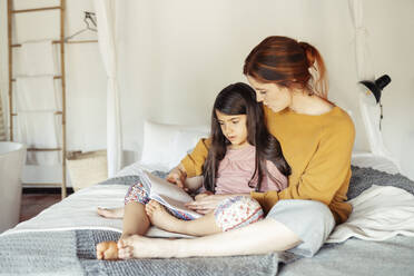 Mother and daughter reading book while sitting on bed at home - JSMF01859