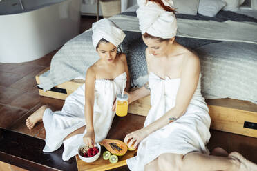 Girl and woman in towel eating fruit while leaning on bed at home - JSMF01865