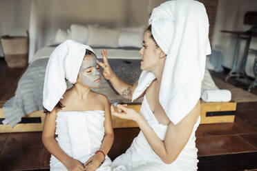 Woman applying facial cream on daughter face while sitting at home - JSMF01871
