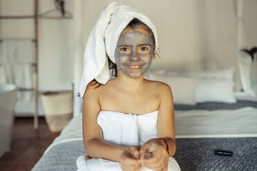 Smiling girl covered in towel with facial mask on face sitting on bed at home - JSMF01874