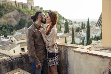 Couple kissing while standing on rooftop - JSMF01883