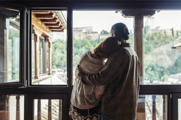 Couple with arm around standing by window at home - JSMF01889
