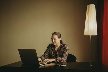 Smiling female entrepreneur working on laptop in office - DMGF00185