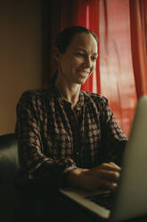 Businesswoman smiling while working on laptop in office - DMGF00191