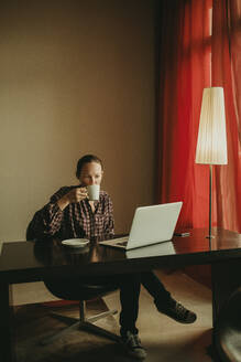 Businesswoman drinking coffee while working on laptop in office - DMGF00197