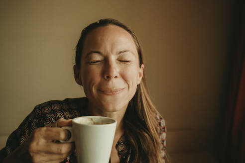 Female entrepreneur drinking coffee while sitting in office against wall - DMGF00200