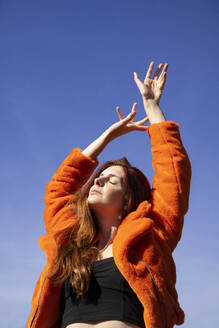 Young woman with eyes closed and hand raised standing against clear sky - AFVF07325