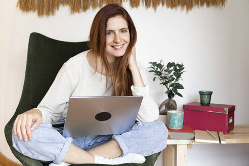 Young woman smiling while sitting with laptop on chair at home - AFVF07328