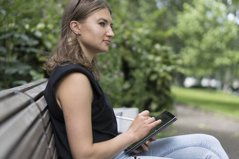 Young woman drawing on graphic tablet while looking away sitting in public park - BOYF01639