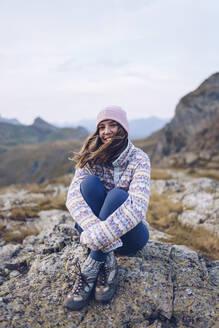 Smiling woman hugging knees while sitting on rock around Ibones of Anayet - RSGF00363