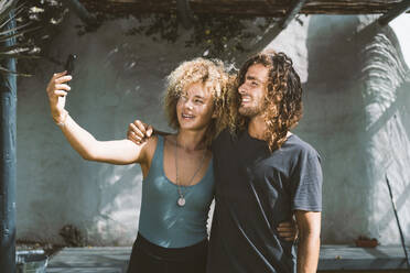 Friends taking selfie through mobile phone while standing outdoors  - DAMF00551