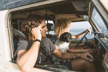 Young woman sitting by dog and man while driving car at beach - DAMF00557