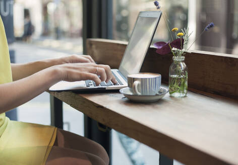 Young businesswoman working on laptop at coffee shop - AJOF00259