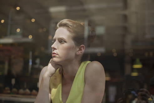 Thoughtful young businesswoman looking through window while sitting in cafe - AJOF00262