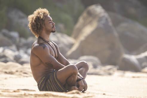 Shirtless young man meditating at beach on sunny day - SNF00629