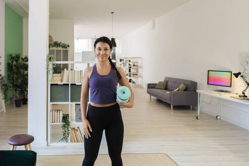 Young female holding exercise mat standing at home - GIOF09164