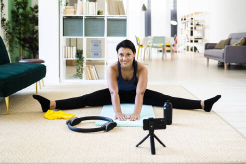 Female influencer video recording on camera while doing stretching exercise at home - GIOF09170
