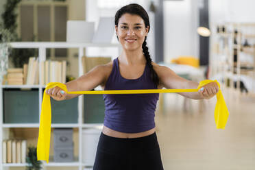 Smiling young fitness female stretching with resistance band standing at home - GIOF09182
