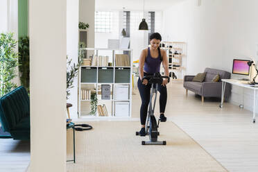 Young woman exercising while sitting on exercise bike at home - GIOF09188