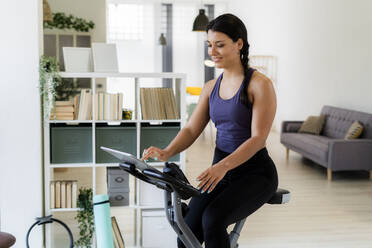 Young woman using digital tablet while sitting on exercise bike at home - GIOF09191