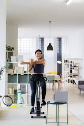 Young female athlete doing stretching exercise while sitting on exercise bike at home - GIOF09194