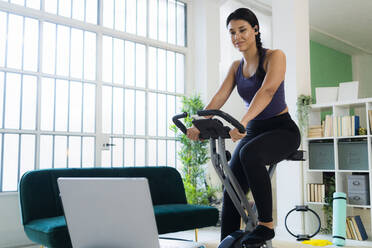 Young woman listening music through bluetooth while sitting on exercise bike at home - GIOF09197