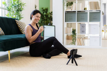 Female influencer showing graphics tablet while video recording on camera at home - GIOF09200