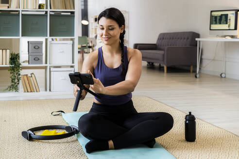 Female athlete with cross legged sitting on exercise mat while video recording at home - GIOF09203