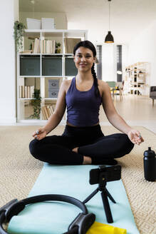 Young woman meditating while video recording on camera at home - GIOF09209