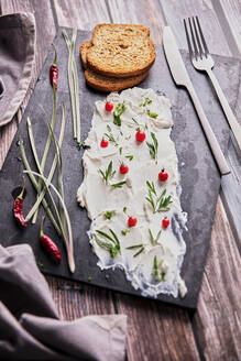 From above of tasty cream cheese and pieces of fresh bread arranged with various herbs on slate board on wooden table - ADSF16620