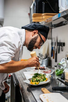 Side view of busy male chef in uniform adding sauce on top of dish with greenery while working in kitchen of cafe - ADSF16650