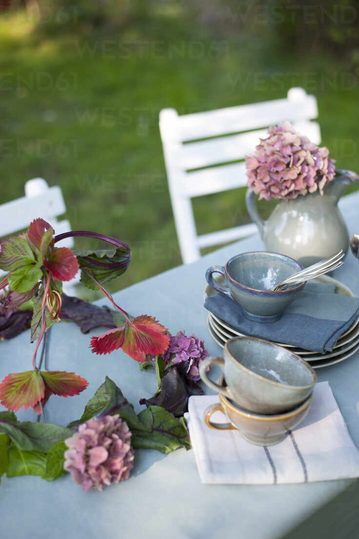 Crockery And Diy Lamp Shade Made Of Leaves And Hydrangea Flowers Lying On Coffee Table Set