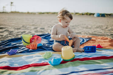Baby boy playing with toys at beach during sunset - GMLF00725